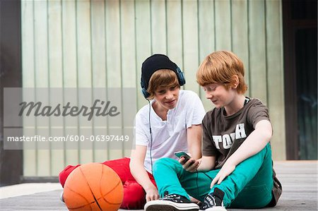 Boys using MP3 Player Outdoors, Mannheim, Baden-Wurttemberg, Germany Stock Photo - Premium Royalty-Free, Image code: 600-06397449