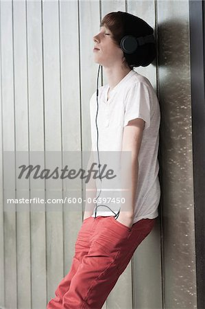 Boy Leaning against Wall and Listening to Music, Mannheim, Baden-Wurttemberg, Germany Stock Photo - Premium Royalty-Free, Image code: 600-06397450