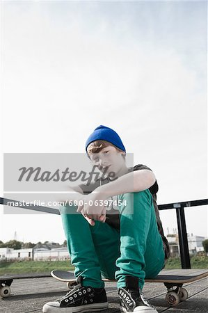 Portrait of Boy Sitting on Skateboard, Mannheim, Baden-Wurttemberg, Germany Stock Photo - Premium Royalty-Free, Image code: 600-06397454
