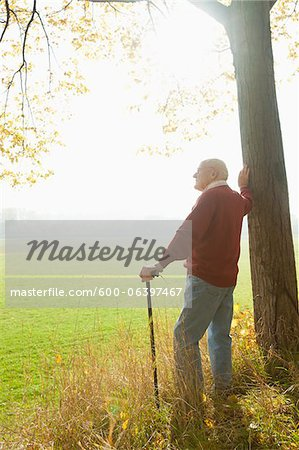 Senior Man with Cane Standing by Tree, Lampertheim, Hesse, Germany Stock Photo - Premium Royalty-Free, Image code: 600-06397467