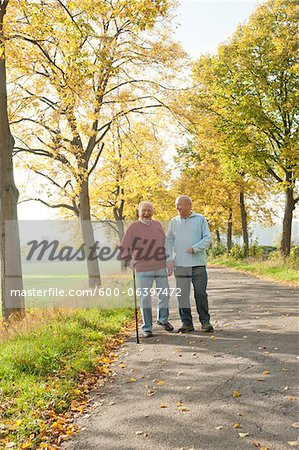 Senior Men Walking on Tree-lined Path in Autumn, Lampertheim, Hesse, Germany Stock Photo - Premium Royalty-Free, Image code: 600-06397472