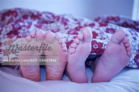 Woman's Feet and Man's Feet Sticking Out of Blanket in Bed, Iceland Stock Photo - Premium Royalty-Free, Image code: 600-06407816