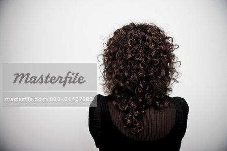 Woman with Curly Brown Hair from the Back in Studio Stock Photo - Premium Royalty-Free, Image code: 600-06407883