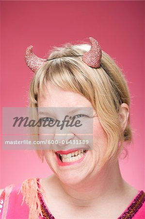 Portrait of Woman Wearing Devil Horns and Scowling Stock Photo - Premium Royalty-Free, Image code: 600-06431389