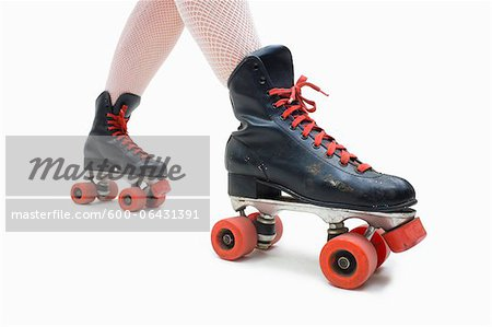 Woman Wearing Fishnet Stockings and Old Fashioned Roller Skates Stock Photo - Premium Royalty-Free, Image code: 600-06431391