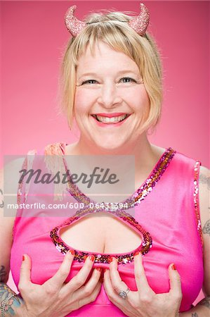 Portrait of Woman Wearing Devil Horns and Holding Her Breasts Stock Photo - Premium Royalty-Free, Image code: 600-06431394
