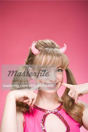 Portrait of Woman Wearing Devil Horns and Making Faces Stock Photo - Premium Royalty-Free, Image code: 600-06431431