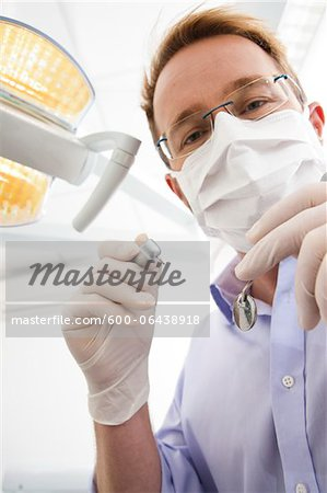 Dentist wearing Surgical Mask and Holding Dental Instruments looking down, Germany Stock Photo - Premium Royalty-Free, Image code: 600-06438918