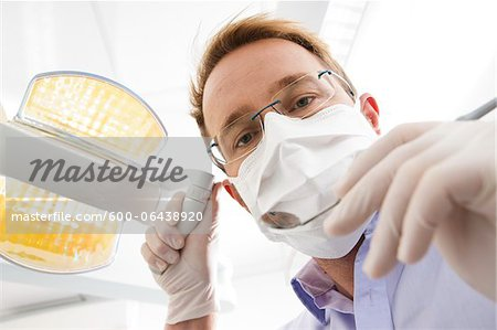 Dentist wearing Surgical Mask Adjusting Light and looking down, Germany Stock Photo - Premium Royalty-Free, Image code: 600-06438920