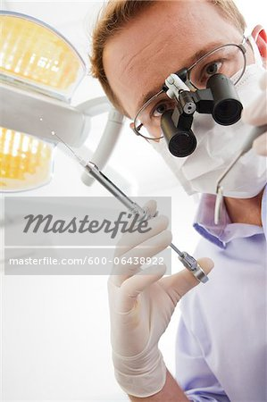 Dentist wearing Surgical Mask and Magnifier holding Needle and looking down, Germany Stock Photo - Premium Royalty-Free, Image code: 600-06438922