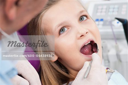 Close-up of Dentist Checking Girl's Teeth during Appointment, Germany Stock Photo - Premium Royalty-Free, Image code: 600-06438930