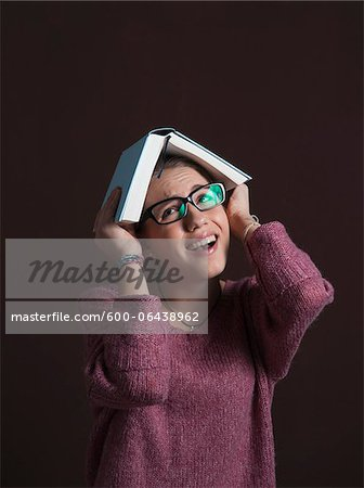 Portrait of Teenage Girl wearing Eyeglasses, holding Open Book over Head with Anxious Expression, Studio Shot on Black Background Stock Photo - Premium Royalty-Free, Image code: 600-06438962