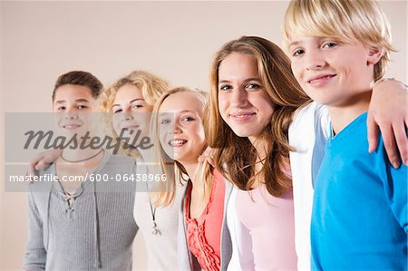 Portrait of Group of Teenage Boys and Girls, Standing in a Row with Arms around Shoulders, Studio Shot on White Background Stock Photo - Premium Royalty-Free, Image code: 600-06438966