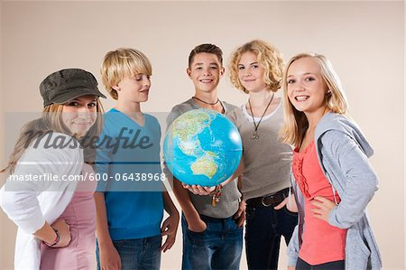 Portrait of Group of Teenage Boys and Girls Holding World Globe, Smiling and Looking at Camera, Studio Shot on White Background Stock Photo - Premium Royalty-Free, Image code: 600-06438968