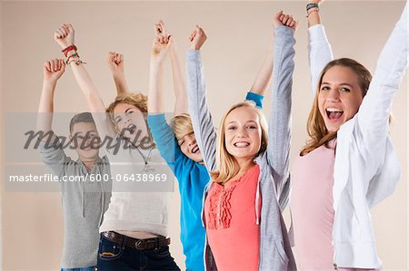 Portrait of Group of Teenage Boys and Girls with Arms in Air, Smiling and Looking at Camera, Studio Shot on White Background Stock Photo - Premium Royalty-Free, Image code: 600-06438969