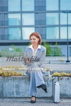 Businesswoman Sitting Outside in front of Office Building using Tablet PC, Niederrad, Frankfurt, Germany Stock Photo - Premium Royalty-Free, Image code: 600-06438975