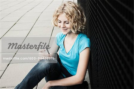 Portrait of Teenage Girl Smiling, Sitting on Sidewalk using Cellphone, Mannheim, Germany Stock Photo - Premium Royalty-Free, Image code: 600-06438976