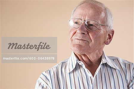 Portrait of Senior Man wearing Aviator Eyeglasses and Looking up into the Distance with Confident Expression in Studio on Beige Background Stock Photo - Premium Royalty-Free, Image code: 600-06438978
