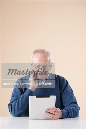 Senior Man Sitting at Table, Looking at Tablet PC, Studio Shot on Beige Background Stock Photo - Premium Royalty-Free, Image code: 600-06438984