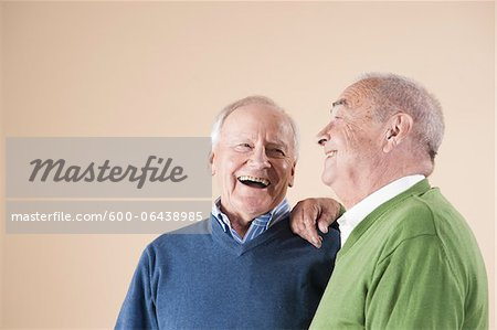 Portrait of Two Senior Men Laughing Together, Studio Shot on Beige Background Stock Photo - Premium Royalty-Free, Image code: 600-06438985