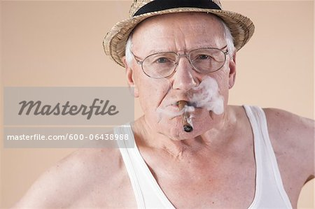 Portrait of Senior Man wearing Undershirt and Straw Hat while Smoking Cigar, Studio Shot on Beige Background Stock Photo - Premium Royalty-Free, Image code: 600-06438988