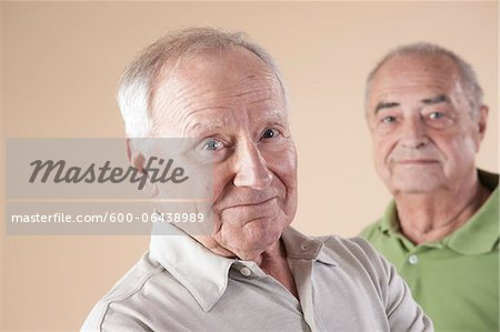 Portrait of Two Senior Men Looking at Camera, Studio Shot on Beige Background Stock Photo - Premium Royalty-Free, Image code: 600-06438989
