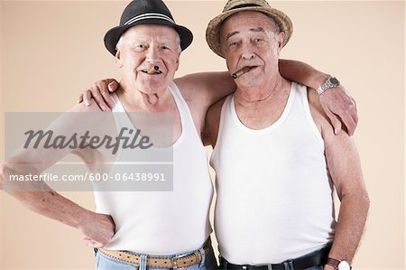 Portrait of Two Senior Man wearing Undershirts and Hats while Smoking Cigars with Arms around Shoulders, Studio Shot on Beige Background Stock Photo - Premium Royalty-Free, Image code: 600-06438991