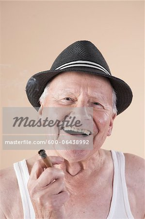Close-up Portrait of Senior Man wearing Undershirt and Hat while Smoking a Cigar and Smiling, Studio Shot on Beige Background Stock Photo - Premium Royalty-Free, Image code: 600-06438992