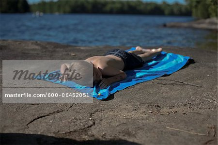 Boy Lying on Beach Towel on Rocks by Lake, Muskoka, Ontario, Canada Stock Photo - Premium Royalty-Free, Image code: 600-06452051