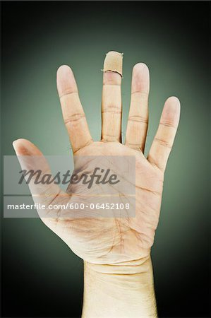 Close-up of Male Left Hand with Bandage on Middle Finger, Studio Shot Stock Photo - Premium Royalty-Free, Image code: 600-06452108