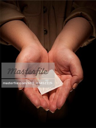 Close-up of Woman's Hands holding Condom, Studio Shot Stock Photo - Premium Royalty-Free, Image code: 600-06452119
