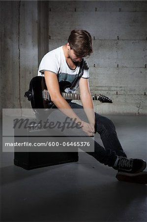 Young Man Holding Electric Guitar Stock Photo - Premium Royalty-Free, Image code: 600-06465376