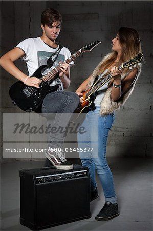 Young Man and Teenage Girl Playing Electric Guitars Stock Photo - Premium Royalty-Free, Image code: 600-06465377