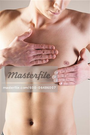 Close-up of Young Man from the Waist up Touching Chest in Studio Stock Photo - Premium Royalty-Free, Image code: 600-06486007