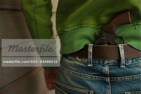 Close-up of Back of Young Man with Handgun Tucked into Waistband of Blue Jeans, Mannheim, Baden-Wurttemberg, Germany Stock Photo - Premium Royalty-Free, Image code: 600-06486015