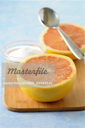Close-up of Grapefruit cut in half with Bowl of Sugar and Spoon on Cutting Board, Studio Shot Stock Photo - Premium Royalty-Free, Image code: 600-06486041