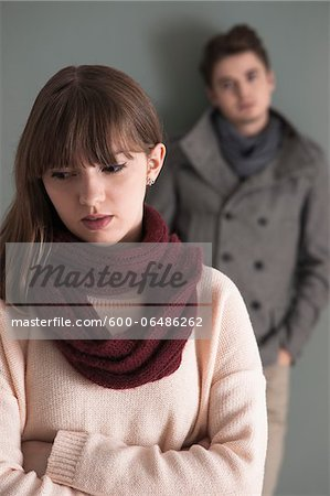 Portrait of Young Man Standing behind Young Woman, Looking at her Intensely, Studio Shot on Grey Background Stock Photo - Premium Royalty-Free, Image code: 600-06486262