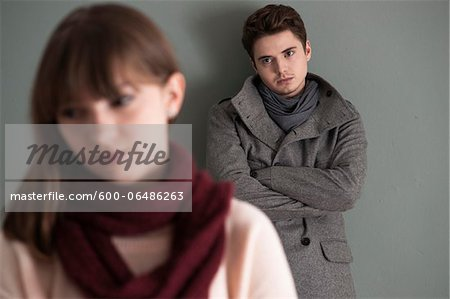 Portrait of Young Man Standing behind Young Woman, Looking at her Intensely, Studio Shot on Grey Background Stock Photo - Premium Royalty-Free, Image code: 600-06486263