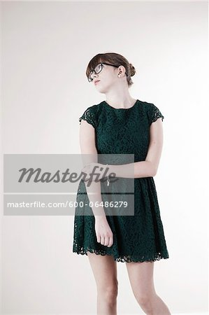 Portrait of Young Woman wearing Green, Lace Dress and Horn-rimmed Eyeglasses, Distracted and Looking Upward, Studio Shot on White Background Stock Photo - Premium Royalty-Free, Image code: 600-06486279