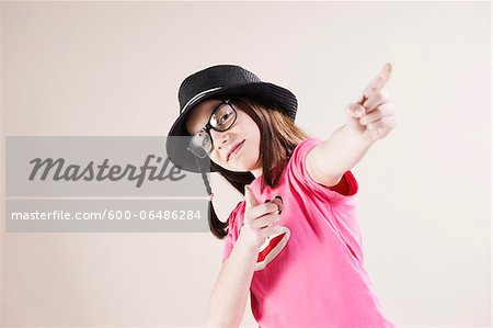 Portrait of Girl wearing Fedora and Horn-rimmed Eyeglasses, Pointing and Smiling at Camera, Studio Shot on White Background Stock Photo - Premium Royalty-Free, Image code: 600-06486284