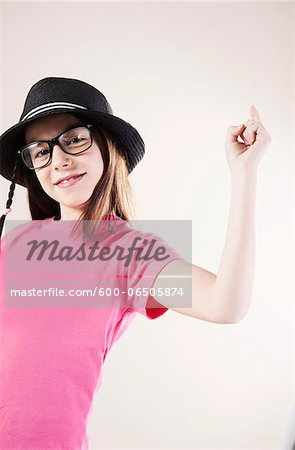 Portrait of Girl wearing Fedora and Horn-rimmed Eyeglasses, Smiling at Camera, Studio Shot Stock Photo - Premium Royalty-Free, Image code: 600-06505874
