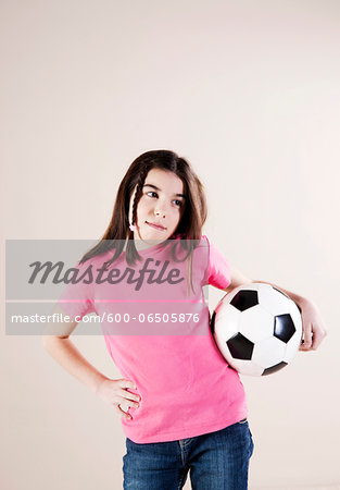 Portrait of Girl with Hand on Hips and Holding Soccer Ball, Looking to the Side, Studio Shot Stock Photo - Premium Royalty-Free, Image code: 600-06505876