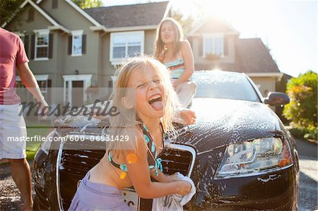 A family washes their car in the driveway of their home on a sunny summer afternoon in Portland, Oregon, USA Stock Photo - Premium Royalty-Free, Image code: 600-06531429