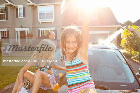 A family washes their car in the driveway of their home on a sunny summer afternoon in Portland, Oregon, USA Stock Photo - Premium Royalty-Free, Image code: 600-06531430