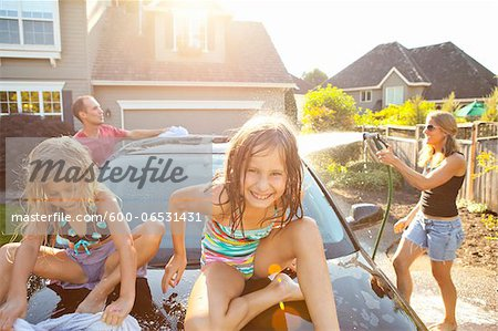 A family washes their car in the driveway of their home on a sunny summer afternoon in Portland, Oregon, USA Stock Photo - Premium Royalty-Free, Image code: 600-06531431