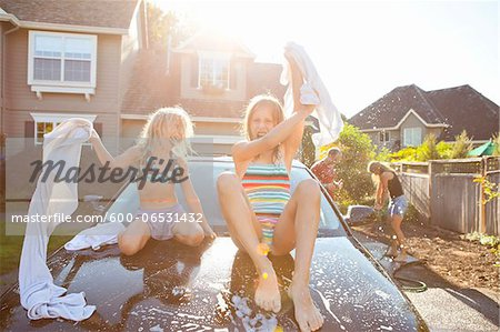 A family washes their car in the driveway of their home on a sunny summer afternoon in Portland, Oregon, USA Stock Photo - Premium Royalty-Free, Image code: 600-06531432