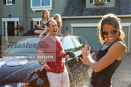 A family washes their car in the driveway of their home on a sunny summer afternoon in Portland, Oregon, USA Stock Photo - Premium Royalty-Free, Image code: 600-06531436