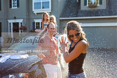 A family washes their car in the driveway of their home on a sunny summer afternoon in Portland, Oregon, USA Stock Photo - Premium Royalty-Free, Image code: 600-06531437