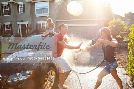 A family washes their car in the driveway of their home on a sunny summer afternoon in Portland, Oregon, USA Stock Photo - Premium Royalty-Free, Image code: 600-06531438