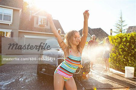 Young girl dances while family washes car in the driveway of their home on a sunny summer afternoon in Portland, Oregon, USA Stock Photo - Premium Royalty-Free, Image code: 600-06531439